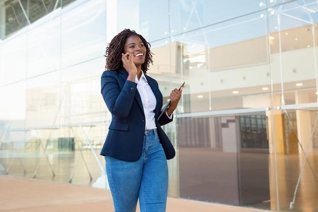 Contenu Femme D'affaires Marchant Et Parlant Par Smartphone Photo gratuit