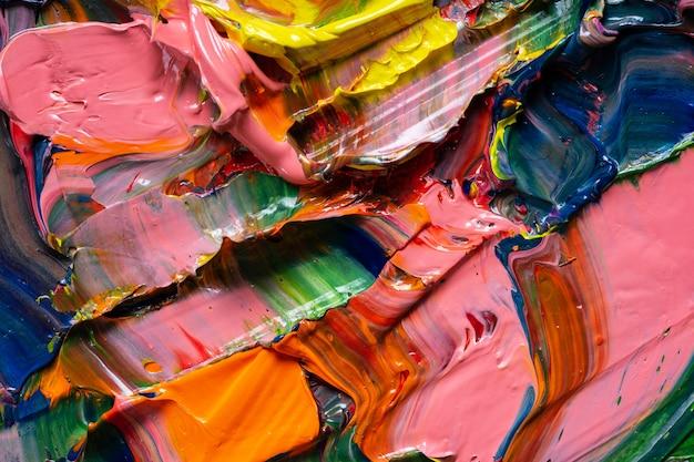 Contexte artistique différentes couleurs vives des peintures à l'huile sont mélangées dans une palette en gros plan. Photo Premium