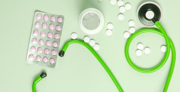 Contexte Créatif Médical Avec Steoscope Et Pilules Sur Fond Vert. Vue De Dessus Photo Premium