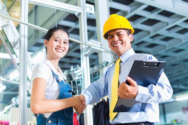 Contremaître asiatique dans une usine textile donnant une formation Photo Premium