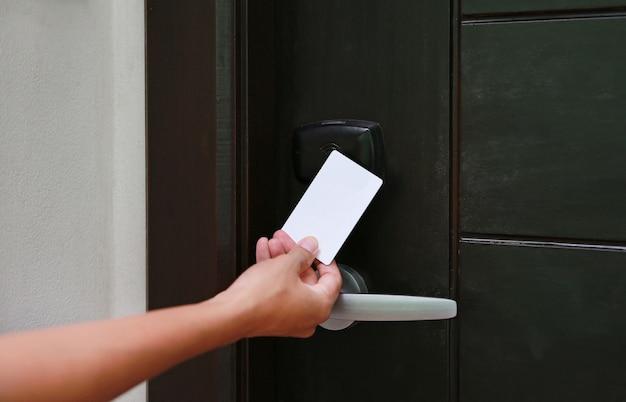 Contrôle d'accès de porte - jeune femme tenant une carte-clé pour déverrouiller la porte Photo Premium