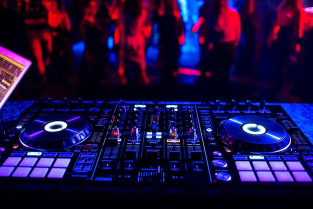 Contrôleur De Musique Dj Mixer Dans Une Discothèque Lors D'une Fête Dans Le Contexte De Silhouettes Floues De Gens Dansants Photo Premium