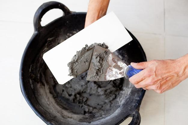 Contruction maçon ouvrier mains avec mortier de ciment Photo Premium