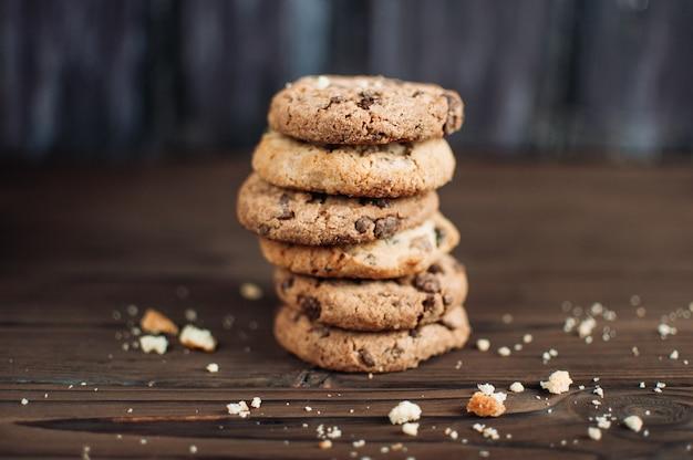 Cookies aux pépites de chocolat empilés sur fond rustique en bois dans un style campagnard Photo Premium
