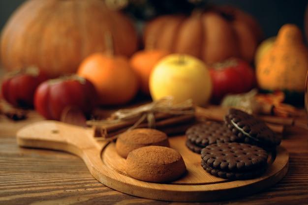 Cookies avec des citrouilles et des pommes sur la table. Photo Premium