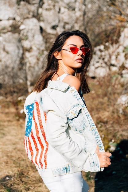 Cool jeune femme en veste en jean et lunettes de soleil Photo gratuit