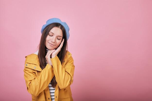 Cool jolie fille en veste de pluie jaune avec les yeux fermés et sourire Photo Premium