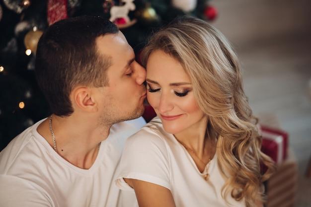 Copain aimant baiser copine près de sapin de noël Photo Premium
