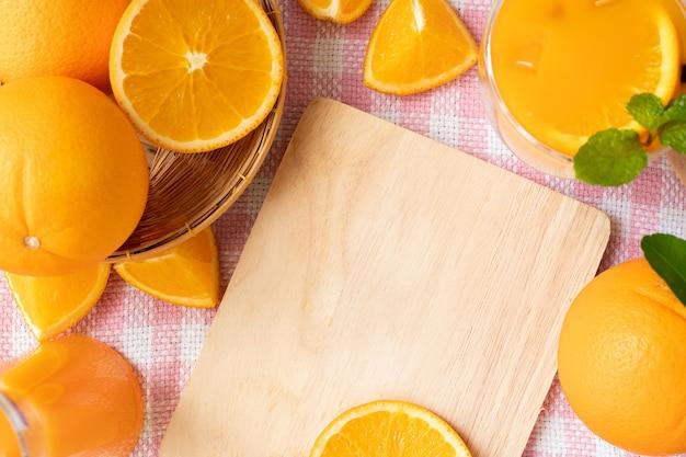 Copiez l'espace sur une planche à découper en bois et un cadre orange. Photo Premium