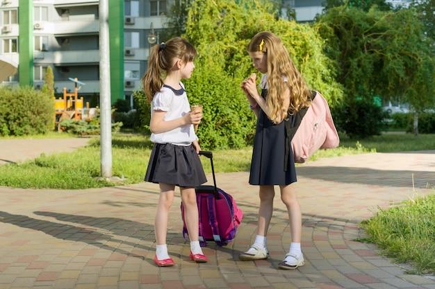 Copines d'écolière avec sacs à dos, manger de la glace Photo Premium