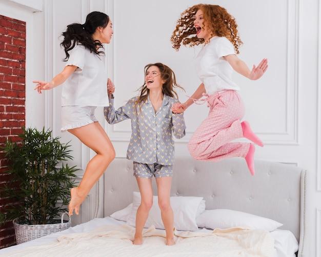 Copines ludiques sauter dans le lit Photo gratuit