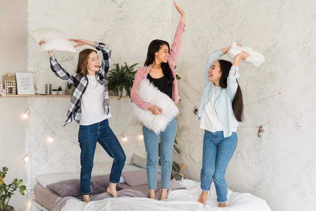 Copines multiethniques s'amuser sur le lit Photo gratuit