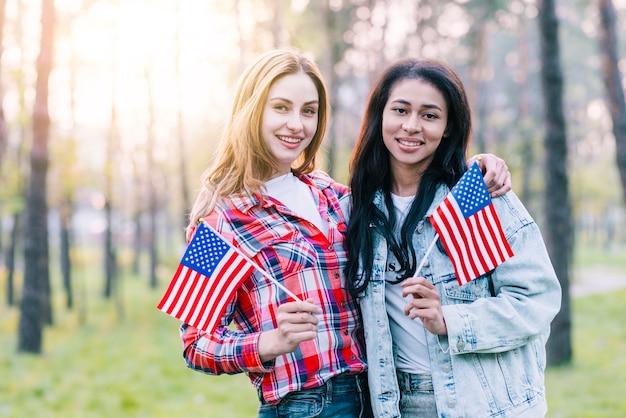 Copines avec petits drapeaux américains debout à l'extérieur Photo gratuit