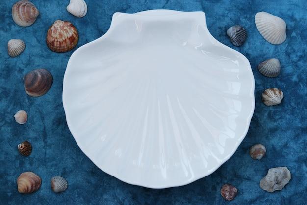 Coquille blanche en style marin sur bleu Photo Premium