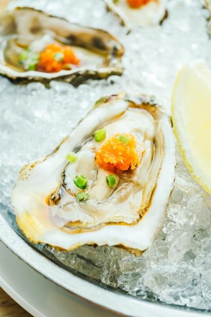 Coquilles d'huîtres crues et fraîches au citron Photo gratuit
