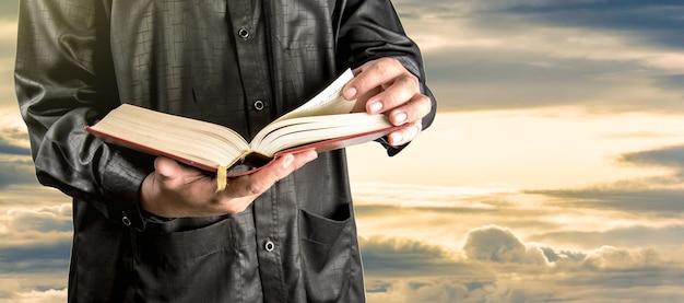 Coran dans la main - livre saint des musulmans Photo Premium