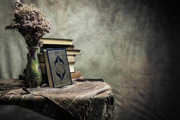 Coran - livre sacré des musulmans (élément public de tous les musulmans) sur la table, nature morte Photo Premium