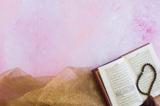 Coran avec des perles sur la nappe Photo gratuit