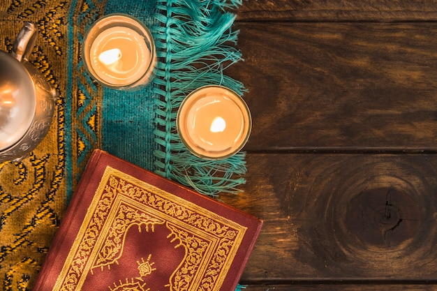 Coran près de bougies allumées et pot Photo gratuit