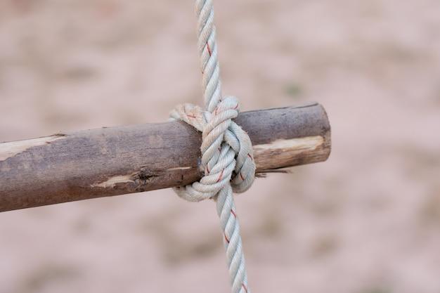 Une corde est nouée autour d'un poteau de clôture, une poteau en bois avec un noeud noué Photo Premium