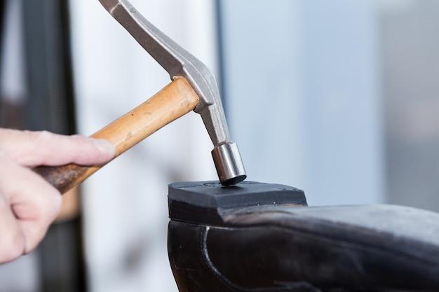 Le cordonnier répare une chaussure Photo Premium