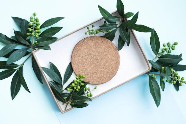 Cork coaster et feuilles dans la boîte sur fond bleu Photo gratuit