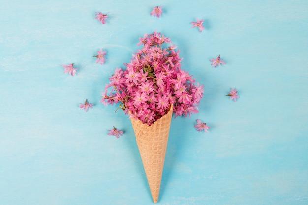 Cornet De Crème Glacée Avec Des Fleurs De Cerisier Rose Ou De Sakura. Concept De Printemps Minimal. Mise à Plat Photo Premium