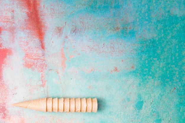 Cornets de crème glacée de wafers vides se rassemblant sur un fond multicolore Photo gratuit
