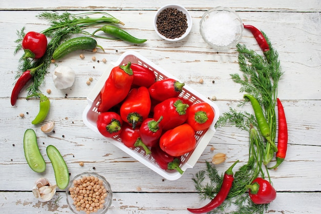 Cornichons sur table en bois blanc avec poivrons verts et rouges, fenouil, sel, grains de poivre noirs, ail, pois, gros plan, concept santé, vue de dessus, vue à plat Photo gratuit