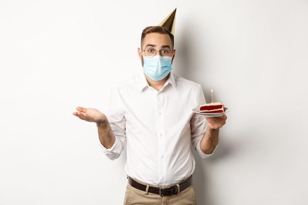 Coronavirus, Quarantaine Et Jours Fériés. Homme Confus En Masque Facial, Tenant Le Gâteau D'anniversaire Et Haussant Les épaules, Debout Sur Fond Blanc Désemparé. Photo Premium
