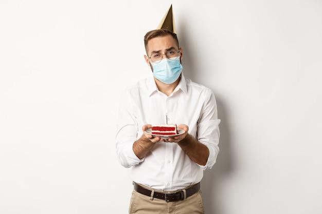 Coronavirus, Quarantaine Et Jours Fériés. Homme Triste Ne Peut Pas Souffler La Bougie Du Gâteau D'anniversaire, Portant Un Masque Facial Et Se Plaignant, Debout Photo gratuit