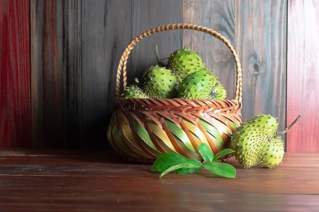 Corossol dans le panier ou la crème épineuse apple ou annona muricata l sur la table en bois Photo Premium
