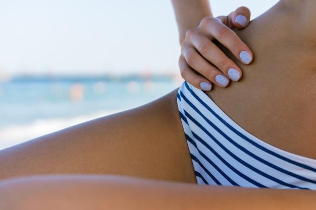 Corps tanné mince femme en maillot de bain sur la plage en gros plan sur un fond d'eau bleue Photo Premium