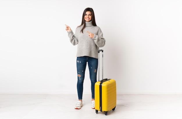 Un Corps Sur Toute La Longueur D'une Femme Voyageant Avec Une Valise Sur Un Mur Blanc Pointant Le Doigt Sur Le Côté Photo Premium