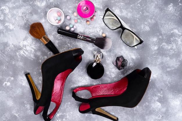 Cosmétiques en parfum et chaussures sur fond gris avec espace de copie Photo Premium