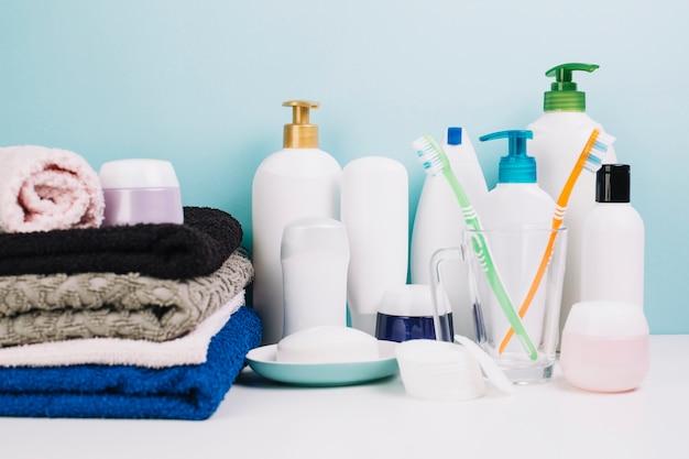 Cosmétiques à proximité des serviettes et des brosses à dents Photo gratuit
