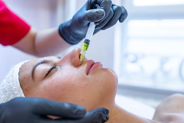 Cosmétologie du matériel, mésothérapie, portrait de jeune femme se faisant traiter la zone du front Photo Premium