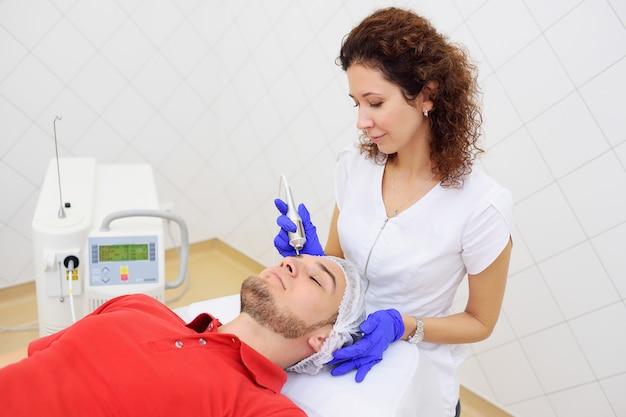 Cosmétologie Laser. Le Médecin Enlève Les Taupes De Pigmentation Ou Verrue Le Patient Au Néodyme Au Laser. Photo Premium