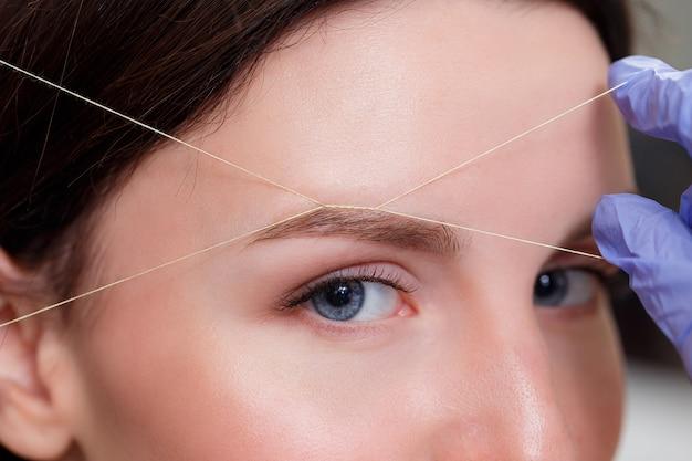 Cosmétologue Plume Les Sourcils Des Clients Par Fil. Fermer Photo Premium