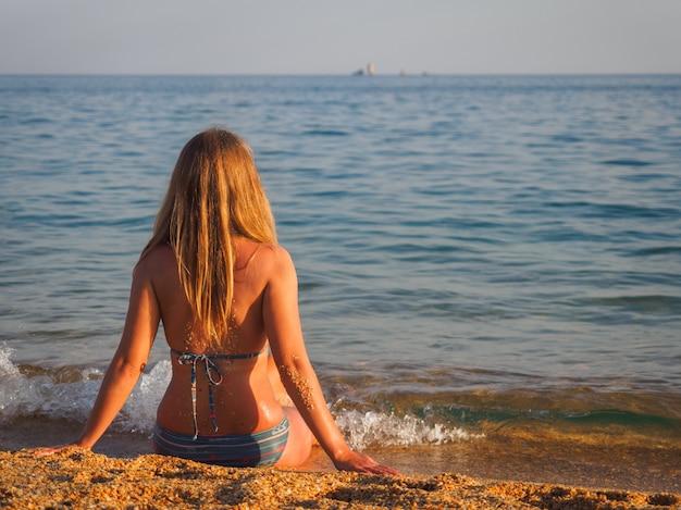 Un costume de fille avec le dos à nous est assis au bord de la mer et le regardant Photo Premium