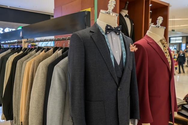 Costumes avec des chemises sur des cintres sur fond en bois Photo Premium