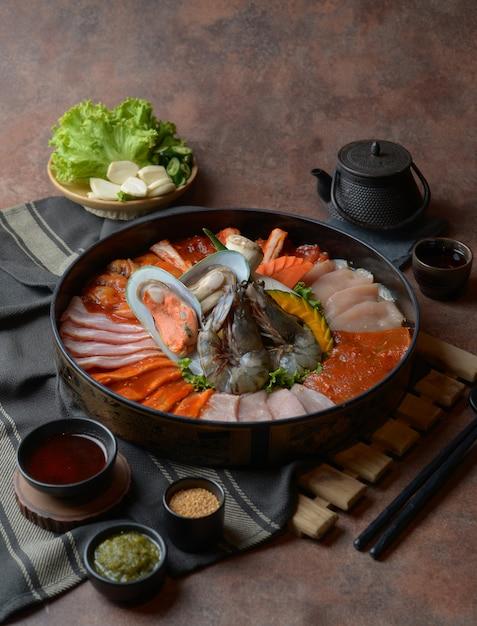 Côte de bœuf garnie de sésame et fruits de mer avec crevettes disposées sur le plateau et légumes pour un grill posé sur la table. Photo Premium
