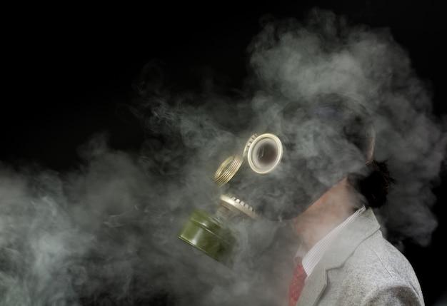 À côté de l'homme dans un masque à gaz avec beaucoup de fumée, désastre environnemental Photo Premium