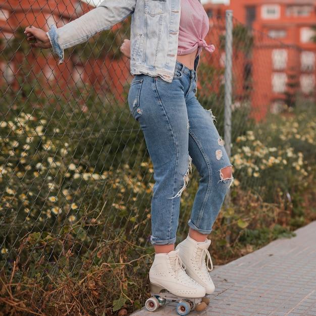 Côté jeune femme portant des patins à roulettes debout près de la clôture Photo gratuit