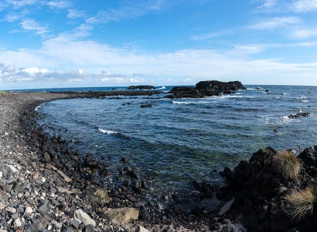 Côte rocheuse dans les açores. vagues éclaboussant sur des roches basaltiques Photo Premium