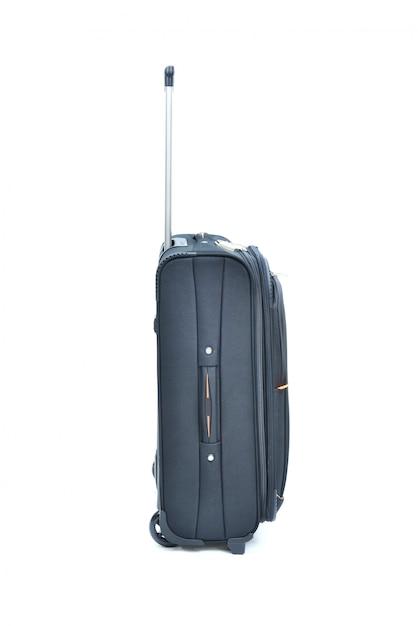 À côté de la valise noire isolée sur blanc Photo Premium