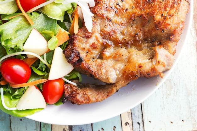 Côtelette de porc au poivre noir avec salade. Photo Premium
