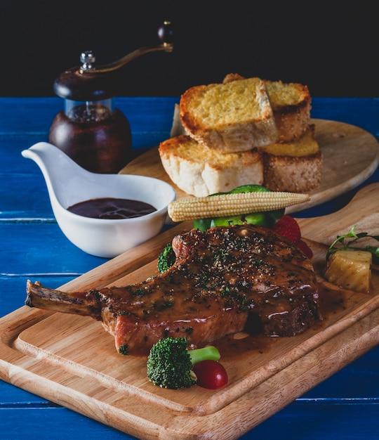 Côtelette De Porc Au Steak Avec Légumes Sur Planche De Bois Photo Premium