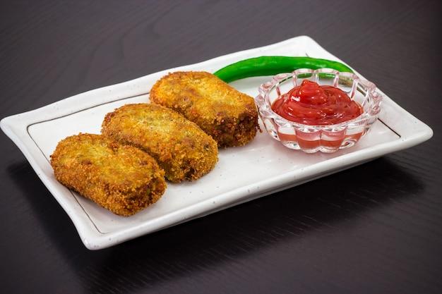 Côtelettes croustillantes frites épicées et dorées, servies avec une sauce tomate ou du ketchup sur une assiette blanche, préparez-vous pour l'iftar ramadan. mise au point sélective Photo Premium