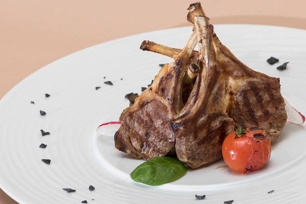 Côtes d'agneau grillées, grillées à la tomate et décorées de radis, de jeunes épinards et de feuilles vertes Photo Premium